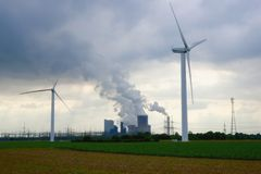 Old and new energy production. Energy technology - wind power wheels and brown coal power plant in the countryside of Rhine-Erft area near Bergheim, Germany Stock Image