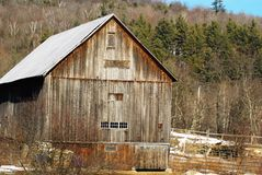 Old New England Wooden barn on a sunny mid winter day. Brown wood, barren trees, snow on field, 4 to 5 stories tall. blue sky stock photo