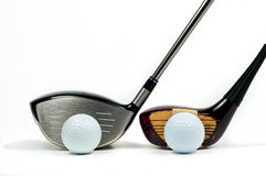 Old and new golf drivers beside one another royalty free stock image