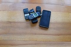 Old and new mobile phones on a wooden table. Mobile phones of various years of release, the end of scientific and technological progress stock photo