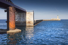 Old and new. Old stell war pillar with the new port entrance in Malta Royalty Free Stock Images