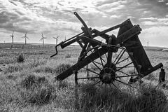 Old and new technology - wind turbines and abandoned plough - black and white Stock Images