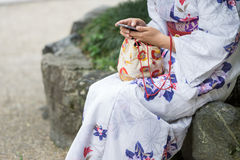 Old and new traditions, Japanese woman with modern phone Stock Photos