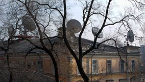 Old and new. View of the roof of an old mansion with many satellite dishes. royalty free stock photo