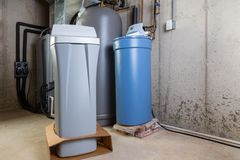 Old and new water softener tanks in a utility room. Waiting for replacement to remove minerals from hard water stock photo