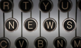 Old News. Close up of old typewriter keyboard with scratched chrome keys with black centers and white letters. Lighting and focus are centered on for keys Stock Images