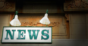 Old News Stand Sign. In city under lights Royalty Free Stock Photography