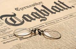 Old newspaper background. Vintage eyeglasses over old newspaper background stock image