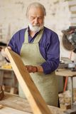 Old nice carpenter with wooden plank at work. Close up vertical shot. small business concept royalty free stock photography