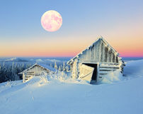 Old nice houses covered with snow in the winter night. The large round orange moon on a blue sky and an old nice houses covered with snow in the winter night Royalty Free Stock Photography