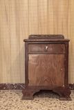 Old nightstand. A very old nightstand with a vintage floor and wall Royalty Free Stock Image