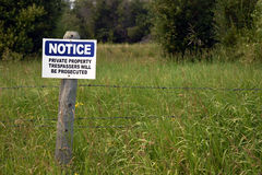Old No Trespassing Sign. An image of a blue and white no trespassing notice posted on a fence post Stock Images
