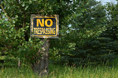 Old No Trespassing Sign. An image of an old yellow and black no trespassing notice posted to a tree Royalty Free Stock Photo