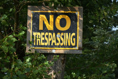 Old No Trespassing Sign. An image of an old yellow and black no trespassing notice posted to a tree Royalty Free Stock Photography