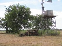 An old north Texas farm complete with windmill and old 1930`s car. stock images