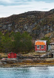 Old Norwegian red wooden houses. On rocky coast Stock Photos
