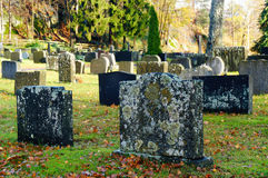 Old Norwegian tombstones. Covered with mosses and lichens. Fallen leaves in a cemetery on a sunny autumn day in the region of Telemark Royalty Free Stock Photos