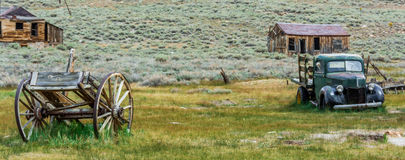 The Old and Not so New. Two modes of conveyance, a cart and an antique truck sitting near each other in a field at the ghost town of Bodie, California Royalty Free Stock Image