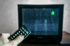 Old not working TV. With white noise snow screen and controller in hand royalty free stock photography