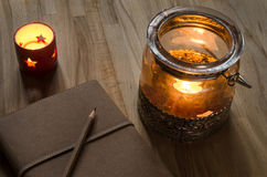 Old notebook with candle lanterns Royalty Free Stock Image