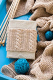 Old notebook with knitted wrap, beige knitted blanket and spokes Royalty Free Stock Image