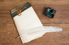 Old notebook, quill ink pen and inkwell on wood ba Royalty Free Stock Image