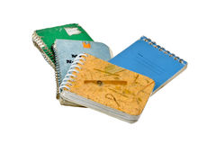 Old Notebooks. Old weathered and worn spiral notebooks. Isolated stock photo