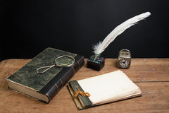 Old notepad, book, quill, magnifying glass royalty free stock photo
