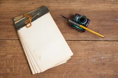 Old notepad, ink pen and inkwell on wooden table stock photo