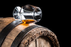 Old oak barrel and a glass of cognac. Isolated on a black background Stock Photos