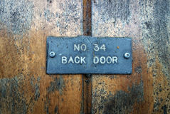Old oak door with back door sign Stock Photography