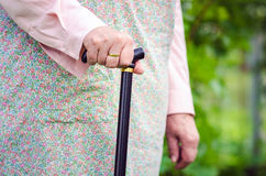 Old obese woman walking with stick. Horizontal Royalty Free Stock Image