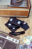Old objects of 70-90 years. Old subjects of 70-90 years: a record player, video of the cartridge, disks, the cartridge and a film on a wooden background Stock Image