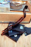 Old objects of 70-90 years. Old subjects of 70-90 years:  record player, video of the cartridge, disks, the cartridge and a film on a wooden background Royalty Free Stock Images
