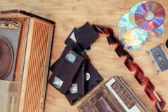 Old objects of 70-90 years. Old subjects of 80-90 years:   video of the cartridge, disks, the cartridge and a film on a wooden background Royalty Free Stock Photo