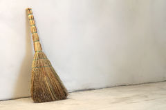 Old obsolete broom or besom leaning on the gray wall Royalty Free Stock Photo