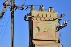 Old and obsolete electrical transformer against the background of a cloudless blue sky. Device for distribution of supply of high. Voltage energy stock photography