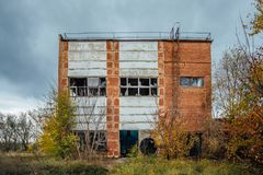 Old obsolete ruined concrete industrial building. Abandoned factory. Concrete ruins in industrial district Royalty Free Stock Images