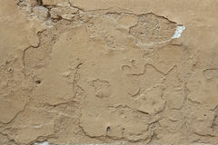 Old ochre painted stucco wall with cracked plaster. Background t Stock Photo