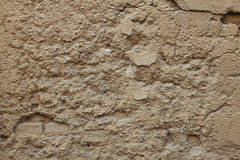 Old ochre painted stucco wall with cracked plaster. Background t Stock Photography