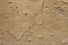 Old ochre painted stucco wall with cracked plaster. Background t Royalty Free Stock Photo