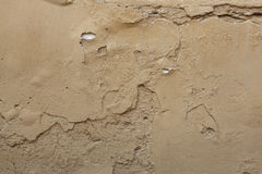 Old ochre painted stucco wall with cracked plaster. Background Stock Photo