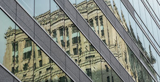 Old office building reflected in the glass of a modern office building Stock Image