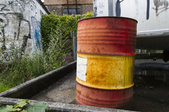 Old Oil Drum. Red and yellow container Stock Photo