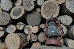 Old oil lamp on the background of firewood stock photography
