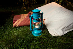 Old oil lamp standing on grass next to pillow and blanket Royalty Free Stock Photos