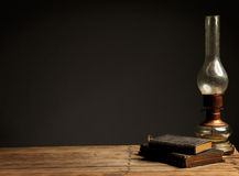 Old oil lamp on a wooden table next to old books Stock Photography