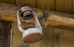Old oil lamp on wooden wall. Old oil lamp hanged on wooden wall Stock Images