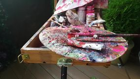 Oil paints the artist at his easel. Old oil paints on easel stock video footage