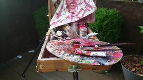 Oil paints the artist at his easel. Old oil paints on easel stock video